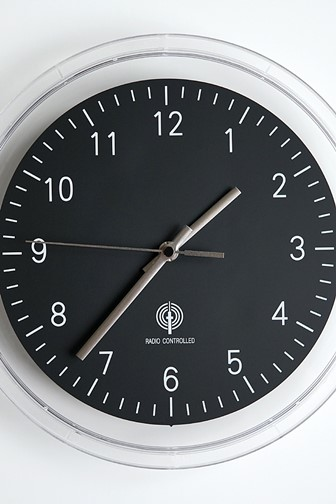 radio controlled wall clock with white numbers on a black clock face